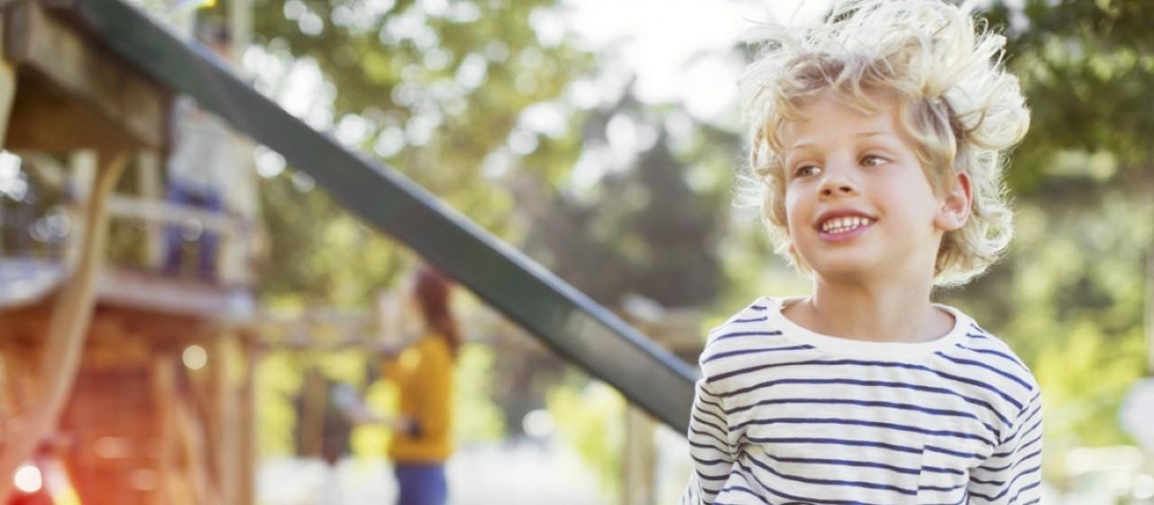 Kinder-Sorglos-Paket, fröhlicher Junge rennt auf Wiese